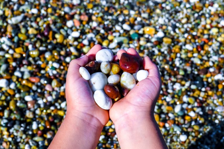 A child hands full of shining colorful seaside stones.