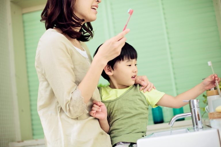 Japanese mother teaching her son to brush his teeth.