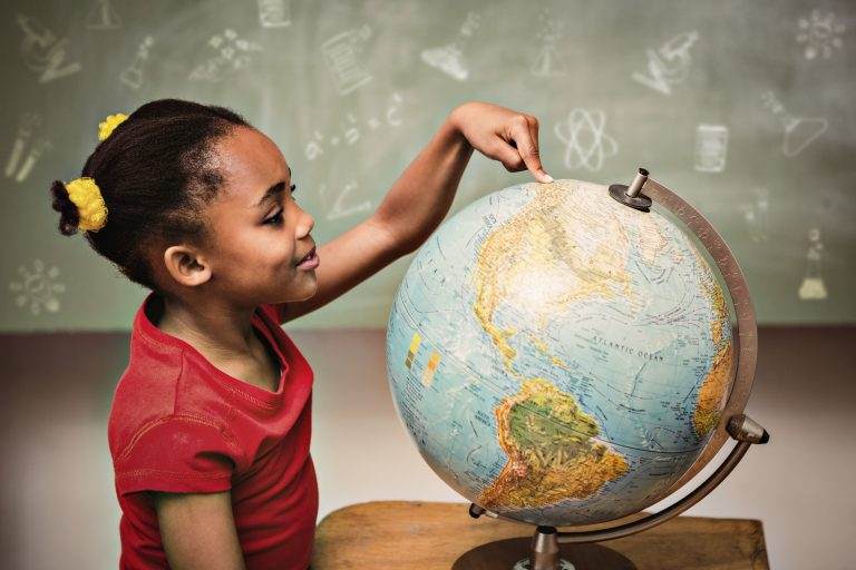School doodles against little girl pointing at globe in classroom
